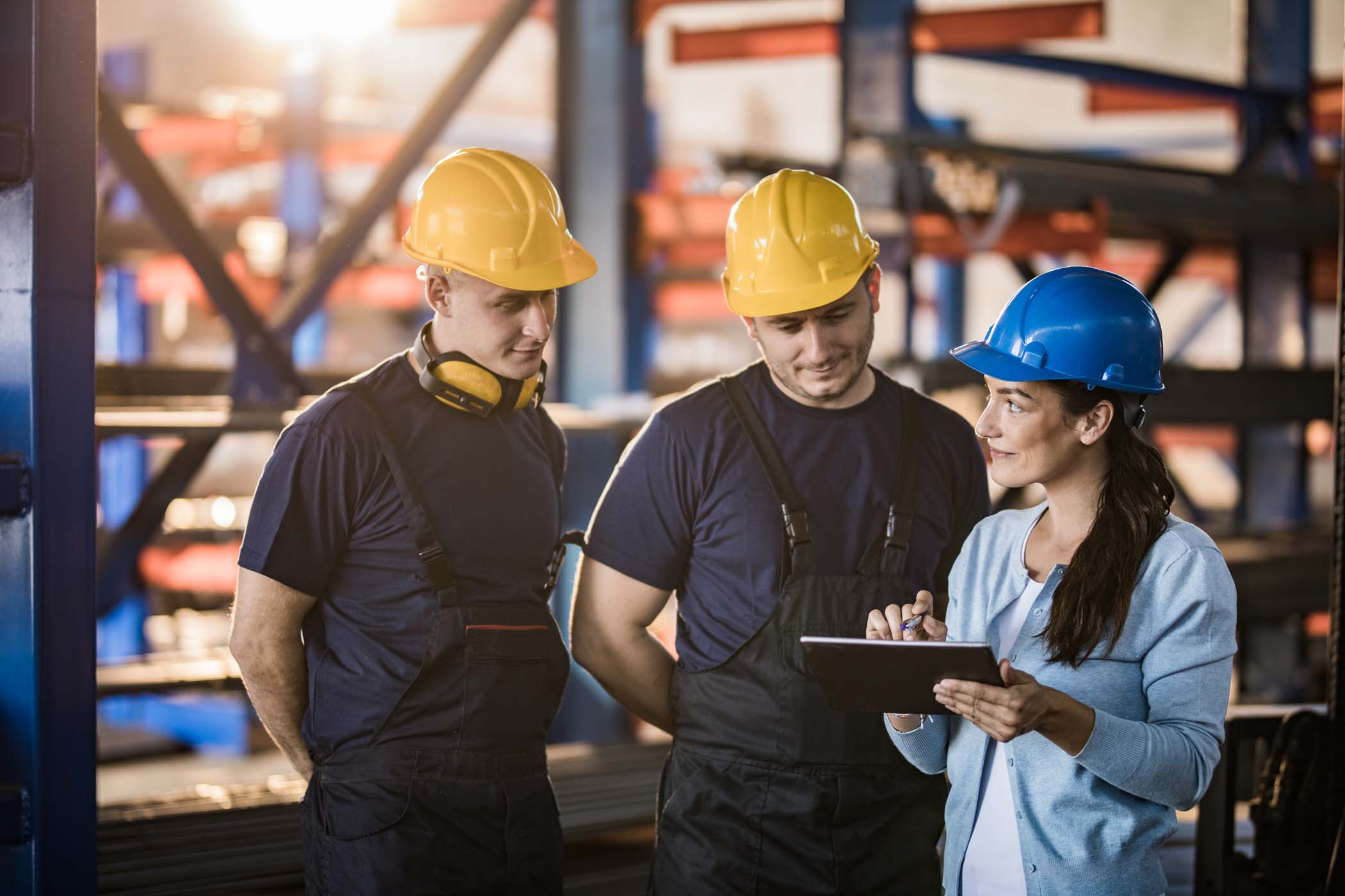 Two manual workers cooperating with female inspector who is working on digital tablet in a warehouse. Focus is on woman.